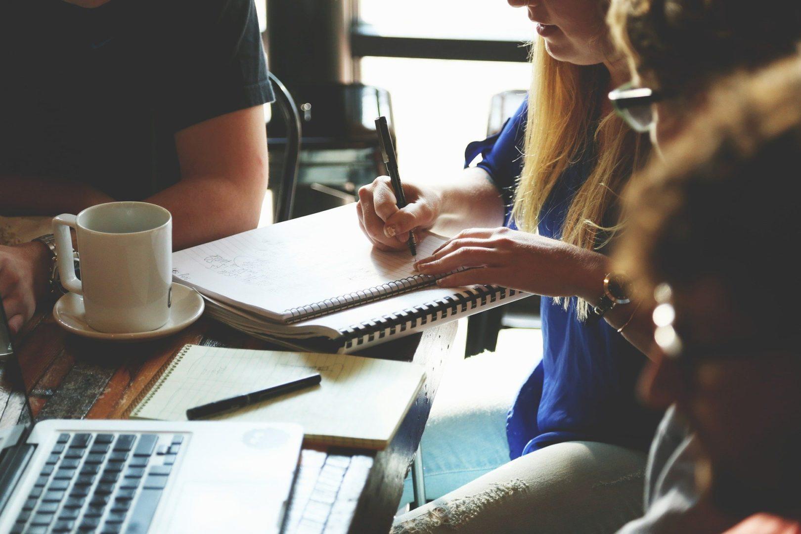 Kilka osób siedzi obok siebie i dyskutują, jedna z kobiet pisze notatki w zeszycie